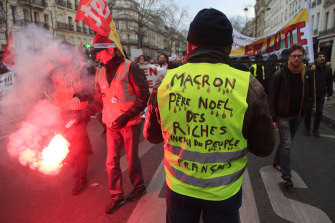 """A Yellow Vest protester attends a demonstration in Paris in December. His vest says """"Macron, Father Christmas to the rich, enemy of the French people""""."""