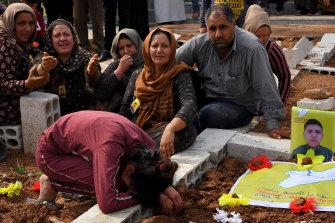 Kurdish mourners bury 19-year-old soldier killed in a Turkish air strike after US forces began their withdrawal from Kurdish territory last week.