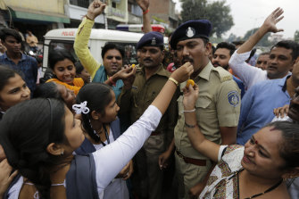 An Indian woman gives a treat to a police officer as the crowd celebrates the police killing of four rape suspects in Shadnagar.