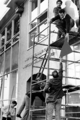Workmen start repairing the damage from the demonstration at the U.S. consulate.