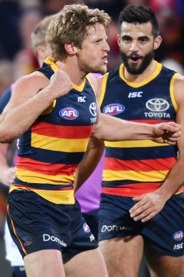 Rory Sloane (left) kicks a goal.