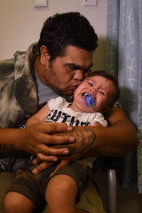 Anthony Dargin, 22, kisses his one-year-old son Ivory after he gets immunisation shots at the Tharawal Aboriginal Corporation Aboriginal Medical Service in Airds.