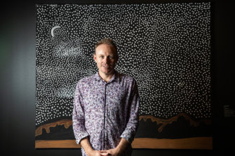 Luke Scholes, curator of Aboriginal Art and Material Culture, Museum and Art Gallery of Northern Territory,  in front of artwork 'Garnkiny' 2019, by Rusty Peters. The artwork won the People's Choice Award.