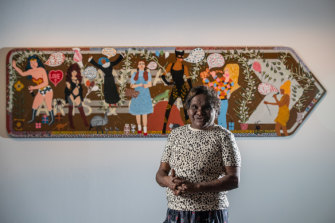Artist Kaylene Whiskey, winner of  the Telstra General Painting Award at the NATSIAAs in front of her work, Seven Sistas.