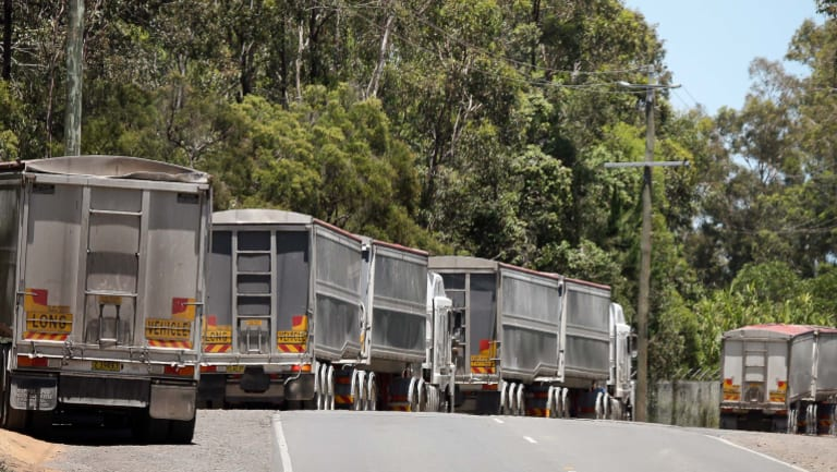 Trucks with NSW licence plates carrying construction waste line up on Sherbrooke Road in Willawong waiting to enter Cleanaway's recycling facility.