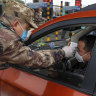 A militia member takes a driver's temperature at a checkpoint at a highway toll gate in Wuhan.