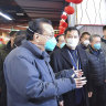 Chinese Premier Li Keqiang, left, speaks with people at a supermarket in Wuhan in central China's Hubei province.