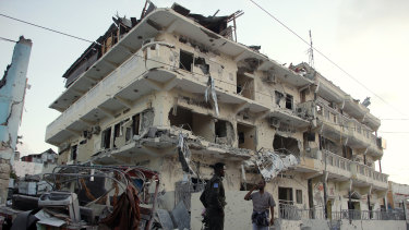 Somali soldiers stand guard at a destroyed building in Mogadishu, Somalia, where terror group al-Shabab has picked up.