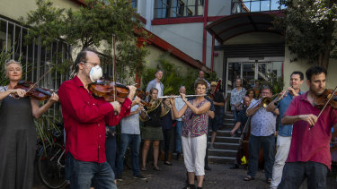 Members of the orchestra of Opera Australia performing with their instruments outside the offices of Opera Australia in March to call on the company to reconsider its decision to stand down musicians without pay.