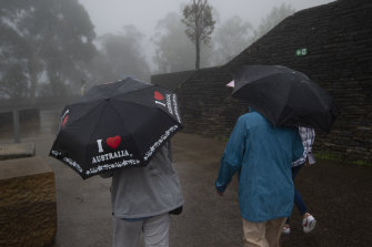 Tourists brave the wet weather at the Three Sisters,  Katoomba on Thursday.