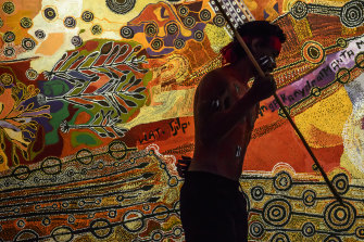 A dancer performs at the unveiling of a vast painting by artists from the Anangu Pitjantjatjara Yankunytjatjara (APY) lands in South Australia at the Australian War Memorial.