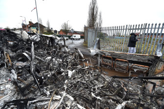 A man walks past a burnt down in Belfast after another night of violence.