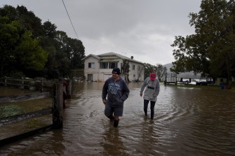 Greg and Amanda Soper walk through the floodwaters on their property near Shoalhaven Heads.