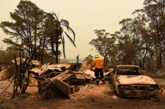 A firefighter inspects a destroyed home at Balmoral, south of Sydney, on Friday.