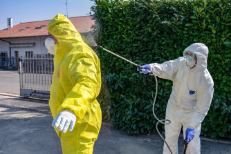 A worker is decontaminated near Bergamo in Italy.