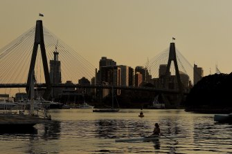 Smoke haze lingers over Sydney as rowers train in Rozelle Bay early on December 4.