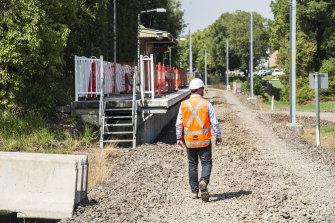 A contruction worker walks along the old Carlingford rail line, which has been torn up to make way for the light rail line.