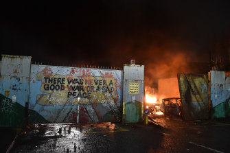 """Cars burn after Nationalists and Loyalists rioted against one another at the """"peace wall"""" interface gates which divide the two communities in Belfast."""