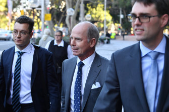 Former IOOF CEO Chris Kelaher (centre) leaves Federal Court.