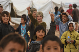Children at the al-Hawl camp raise their index fingers to the sky in a sign for monotheism adopted by Islamic State followers.