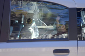 A man is given oxygen in a car parked outside a hospital in Naples.
