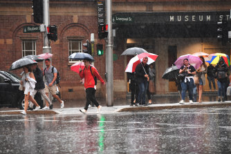 Pedestrians hold umbrellas outside Museum Station on Friday morning.