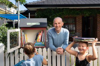Adrian Perillo-Phipps and his children Thomas and Alice have a street library in their front yard to share books with their community.