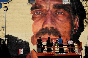 A group of artists paint a mural of Adam Goodes on the wall of a building on the corner of Foveaux Street and Crown Street in Surry Hills.