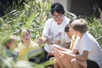 Aunty Maxine teaches kids about bush food in the Chifley Public School garden.