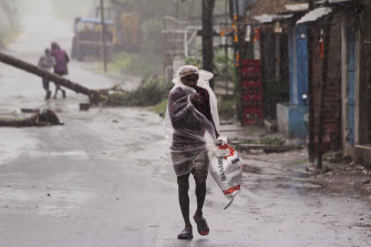 A man covers himself with a plastic sheet and walks in the rain before Cyclone Amphan made landfall.