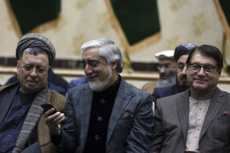 Afghan presidential candidate Abdullah Abdullah (centre) looks at his phone during a press conference in Kabul on Sunday.