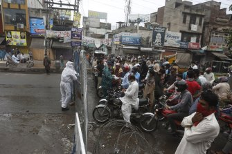 Police officers stop motorcyclists from entering a restricted area that is sealed off to control the spread of the coronavirus in Lahore, Pakistan.