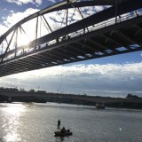 Cr Schrinner is lowered into a dinghy after swinging underneath the Goodwill Bridge.