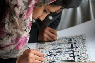 A woman at Kabul's Turquoise Mountain school practises her calligraphy.