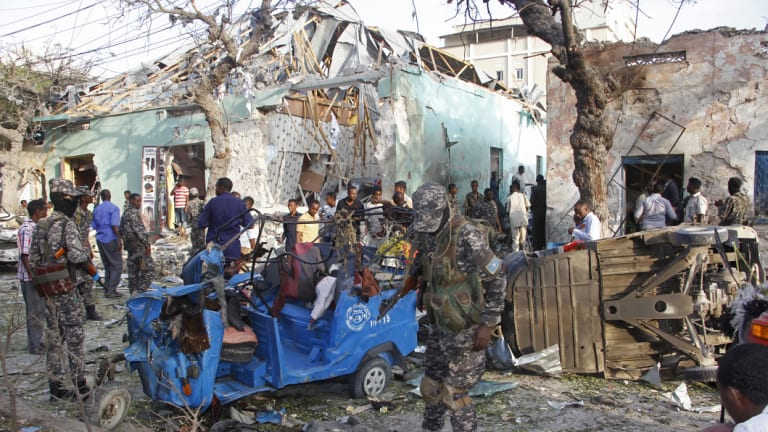 People stand outside a destroyed building after a car bomb in Mogadishu, Somalia, in March. The road has been a target of attacks in the past by the Somalia-based extremist group al-Shabab, the deadliest Islamic extremist group in Africa.