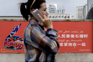 URUMQI, XINJIANG UYGUR AUTONOMOUS REGION, CHINA - 2016/06/19: A young Uygur girl makes a phone call with her iPhone while walking past a propaganda wall, on which writes 'All different peoples should unite together just like pomegranate seeds. (Photo by Zhang Peng/LightRocket via Getty Images) Getty image for Traveller. Single use only.