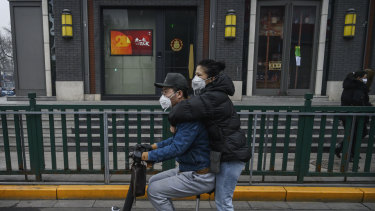 A Chinese couple wear protective masks as they ride a scooter in Beijing on Thursday.