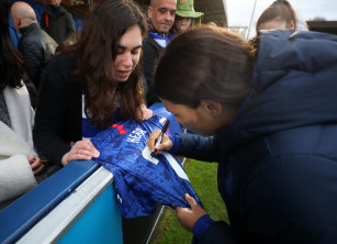 Sam Kerr signs a fan's shirt after Chelsea's win.