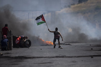 A protester waves the Palestinian flag during clashes with the Israeli forces at the Hawara checkpoint.