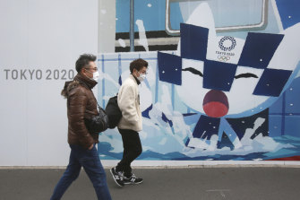 People walk by posters promoting the Olympic and Paralympic Games in Tokyo.
