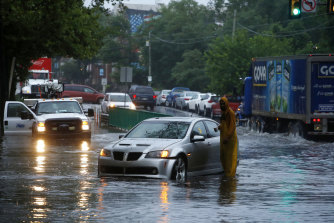 A man checks on a stranded vehicle during Tropical Storm Isaias.
