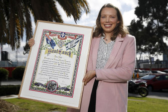 Molly Couch, Paul's daughter, with the Brownlow certificate presented to the family by the AFL earlier this month.