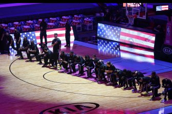 Boston players kneel in protest before their NBA match against Miami.