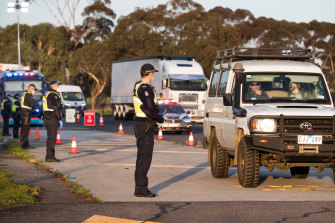 Police wearing masks and gloves stop drivers at a checkpoint on the Hume Freeway.