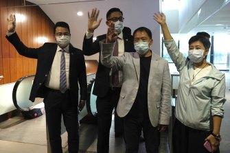 Pro-democracy legislators, from right, Wong Pik Wan, Wu Chi Wai, Lam Cheuk-ting, Yoon Siu Kin wave after handing their letters at the Legislative Council in Hong Kong.