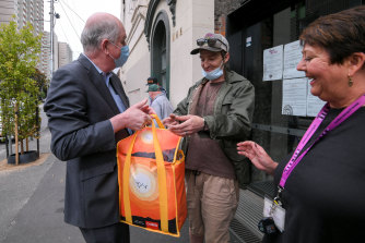 Housing Minister Richard Wynne was at St Mary's House of Welcome in Fitzroy on Chrismas Eve where, with chief executive Robina Bradley, he handed food hampers to clients including Drew Millar.