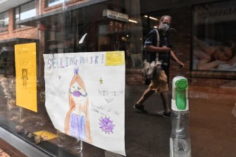 A child's drawing on a window shop encourages shoppers to buy and wear masks.