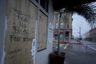 The Shark Shack Beach Bar and Grill is boarded up on Strand Street in Galveston.