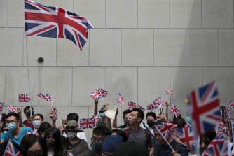 Protesters wave British flags and participate in a peaceful demonstration outside the British Consulate in Hong Kong on Sunday.
