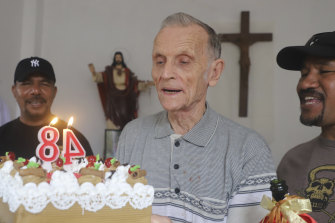 Daschbach, centre, is presented with a cake to celebrate his 84th birthday in Dili in January.